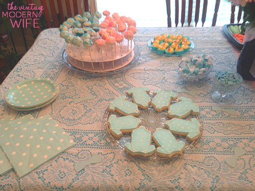 The blue side of this gender reveal table has blue onesie cookies from Sweet Elise bakery in Austin, Texas, pink and blue cake pops, blue deviled eggs, candies, and plates with napkins. Perfectly simple!