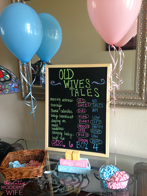 Love the set up of the entry table for The Vintage Modern Wife's gender reveal party using this old wives tales chalkboard, balloons, candy, and bows for guests to pick their guess of the gender!