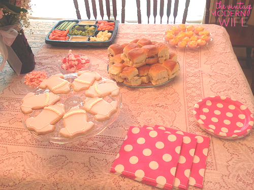 The pink side of this gender reveal able has pink onesie cookies from Sweet Elise bakery in Austin, Texas, pink deviled eggs, sandwiches and veggies, and plates with napkins. So cute!