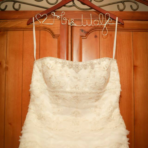 The Vintage Modern Wife shows off her wedding dress details with this custom bridal hanger to hold her dress!